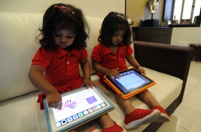 Twins play with the iPad